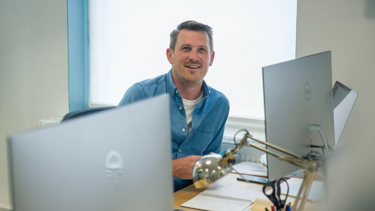 Andy sitting in the Brightec office smiling as he thinks about leading a remote team
